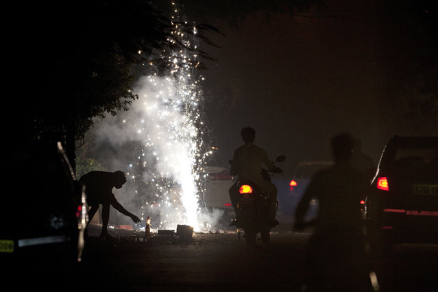Indians play with firecrackers to celebrate Diwali in Hyderabad, India, Thursday, October 19, 2017. Hindus light lamps, wear new clothes, exchange sweets and gifts and pray to goddess Lakshmi during Diwali, the festival of lights. (Photo by Mahesh Kumar A./AP Photo)