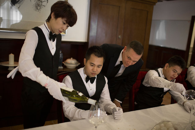 Christopher Noble, an instructor at The International Butler Academy China, teaches students to pour wine on September 16, 2014 in Chengdu, China.  (Photo by Taylor Weidman/Getty Images)