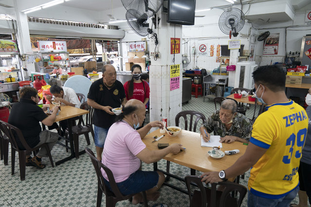 Customers have breakfast at a local restaurant in Kuala Lumpur, Malaysia, on Monday, May 4, 2020. Many business sectors reopened Monday in some parts of Malaysia since a partial virus lockdown began March 18. The easing of restrictions, days before the lockdown was due to end May 12, came as Prime Minister Muhyiddin Yassin's government sought to balance between curbing the virus and reviving the hard-hit economy. (Photo by Vincent Thian/AP Photo)