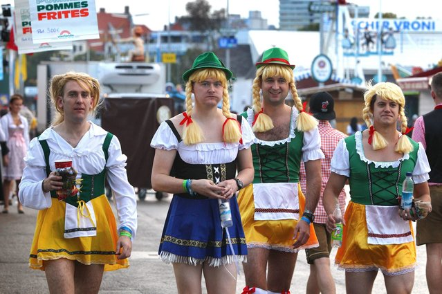 British visitors wearing Bavarian costumes walk ahead the opening of the traditional Bavarian Oktoberfest festival at the Theresienwiese in Munich, southern Germany, on September 20, 2014. (Photo by Karl-Josef Hildenbrand/AFP Photo/DPA)