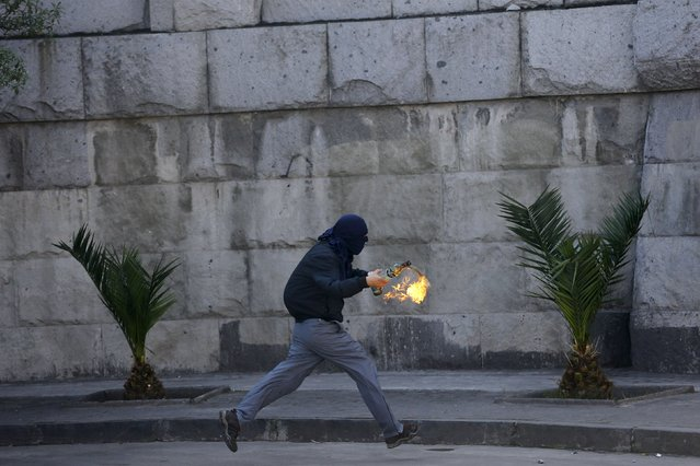 A hooded demonstrator prepares to throw a Molotov cocktail against riot policemen during a protest marking the country's 1973 military coup, in Santiago, Chile September 13, 2015. (Photo by Ivan Alvarado/Reuters)