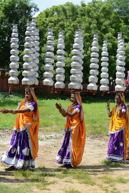 """Indian folk-dancers of Ambawadi Kala Vrund from Jamkhambhaliya town rehearse the traditional dance, """"Bavan Beda No Raas"""" – carrying 52 utensils – prior to performing at a function in Ahmedabad on September 24, 2014. The folk-dancers, who work as daily wage farm labourers, will perform at a function organised by the Gujarat Lok Kala Foundation in Ahmedabad. (Photo by Sam Panthaky/AFP Photo)"""