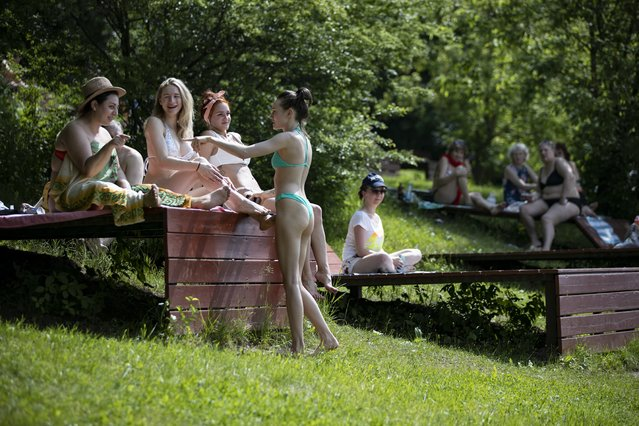 People rest at a one of parks by the Moscow River during a hot day in Moscow, Russia, Tuesday, June 9, 2020. The Russian capital on Tuesday has ended a tight lockdown in place since late March, citing a slowdown in the coronavirus outbreak. Starting from Tuesday, Moscow residents are no longer required to self-isolate at home or obtain electronic passes for traveling around the city. (Photo by Alexander Zemlianichenko/AP Photo)