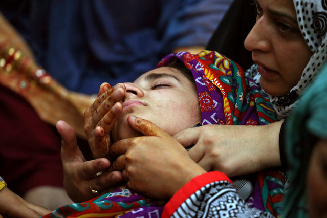 Relatives of Irfan Ahmed, who according to local media died after being hit by a tear gas canister fired by security forces, mourn his death in Srinagar as the city remains under curfew following weeks of violence in Kashmir, August 22, 2016. (Photo by Cathal McNaughton/Reuters)