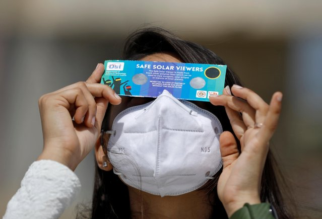 A woman, wearing a protective face mask against the coronavirus disease (COVID-19), uses solar viewers to watch a partial solar eclipse at Gandhinagar, India, June 21, 2020. (Photo by Amit Dave/Reuters)