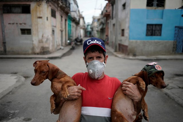 Roberto Gonzalez, who produces mini shows for tourists with his two Dachshunds, poses for a photo in front of his home amid concerns about the spread of the coronavirus disease (COVID-19), in downtown Havana, Cuba, May 18, 2020. (Photo by Alexandre Meneghini/Reuters)