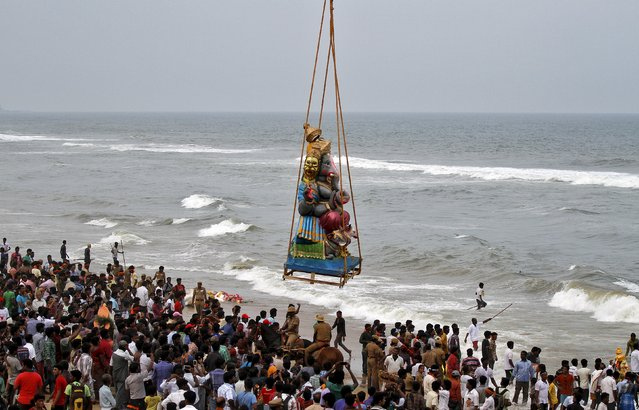 A crane lowers an idol of the Hindu god Ganesh, the deity of prosperity, into the Bay of Bengal for its immersion during the ten-day-long Ganesh Chaturthi festival in Chennai, India, September 20, 2015. (Photo by Reuters/Stringer)