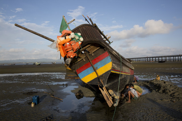In this September 21, 2017, local villagers repair a fishing boat in Shah Porir Dwip, an island by the Bay of Bengal at Bangladesh's southern tip. This island can mean both hope and death for the Rohingya Muslims who are desperate to escape the violence that has engulfed their lives in Myanmar's Rakhine state. High tide or low, day or night, rough waters or calm, when they can find a boat, the Rohingya take their chance to flee to Bangladesh. More than 430,000 have left Myanmar in less than a month. (Photo by Bernat Armangue/AP Photo)