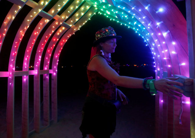 Erin Searcy explores an art installation as approximately 70,000 people from all over the world gather for the 30th annual Burning Man arts and music festival in the Black Rock Desert of Nevada, U.S. August 29, 2016. (Photo by Jim Urquhart/Reuters)