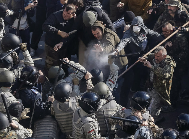 Radical protesters clash with law enforcement members on the Day of Ukrainian Cossacks, marked by activists and supporters of the All-Ukrainian Union Svoboda (Freedom) Party and far-right activists and nationalists to honour the role of the movement in the history of Ukraine, during a rally near the parliament building in Kiev, October 14, 2014. The radical protesters demanded the release of political prisoners in Ukraine. (Photo by Gleb Garanich/Reuters)