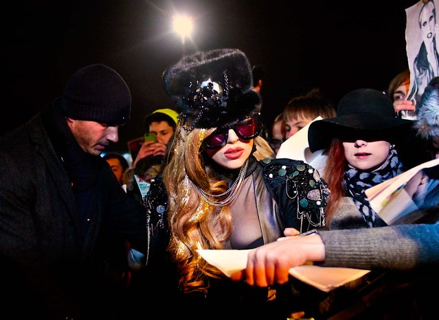 Lady Gaga signs autographs as she arrives at Vnukovo airport outside Moscow for her upcoming performance at Olimpiisky stadium, December 10, 2012. (Photo by Pavel Golovkin/Associated Press)