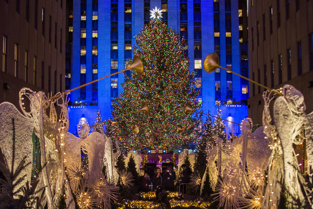 In this November 29, 2017, file photo, the Rockefeller Center Christmas tree stands lit as people take photos of it and the holiday decorations at Rockefeller Center during the 85th annual Rockefeller Center Christmas tree lighting ceremony in New York. For the past decade, old Rockefeller Center Christmas trees have gone on to be milled into lumber used in dozens of Habitat for Humanity homes from Philadelphia to Pascagoula, Mississippi. (Photo by Andres Kudacki/AP Photo)
