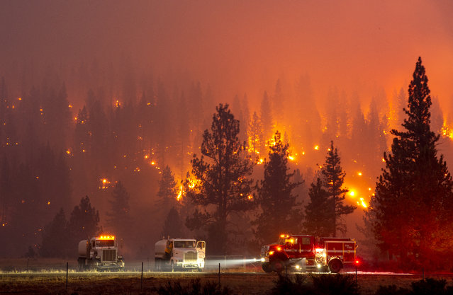 In this long exposure photograph, firefighters mop up hot spots from the Hog fire along highway 36 about 5 miles from Susanville, California on July 20, 2020. The fire exploded to more than 6,000 acres and created its own weather, generating lightning, thunder, rain and fire whirls out of a huge pyrocumulonimbus ash plume towering above. The Lassen County Sheriff's office issued a mandatory evacuation order for the area. (Photo by Josh Edelson/AFP Photo)