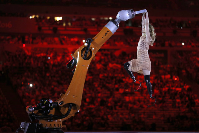 In this Wednesday, September 7, 2016 photo, amputee Amy Purdy dances with a robot during the opening ceremony of the Paralympic Games at Maracana Stadium in Rio de Janeiro, Brazil. (Photo by Mauro Pimentel/AP Photo)