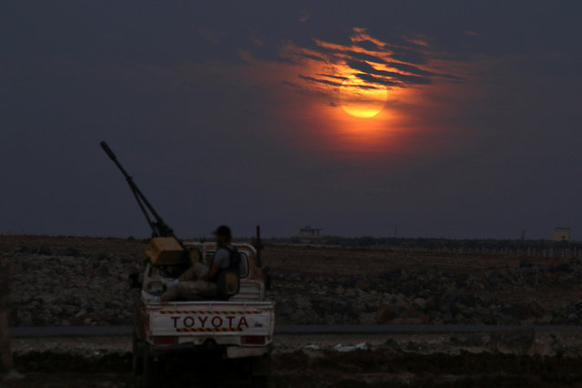A Free Syrian army fighter sits on a pick-up truck mounted with a weapon, as the supermoon partly covered by clouds is seen in the background, in the west of the rebel-held town of Dael, in Deraa Governorate, Syria on November 14, 2016. (Photo by Alaa Al-Faqir/Reuters)