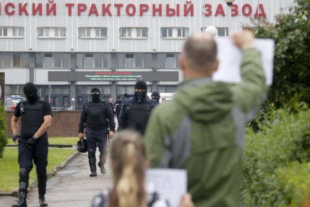 """Protesters stand in front of the Minsk Tractor Works Plant holding posters supporting workers as police walk to push them back in Minsk, Belarus, Wednesday, August 19, 2020. Workers at state-controlled companies have joined strikes this week, as the unprecedented mass protests enter their 11th day and erode the authority of the man once dubbed """"Europe's last dictator"""". (Photo by Dmitri Lovetsky/AP Photo)"""