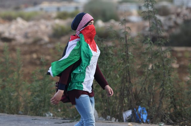 A masked Palestinian girl, draped in a Palestinian flag, walks during clashes with Israeli troops near the Jewish settlement of Bet El, near the West Bank city of Ramallah October 8, 2015. (Photo by Mohamad Torokman/Reuters)