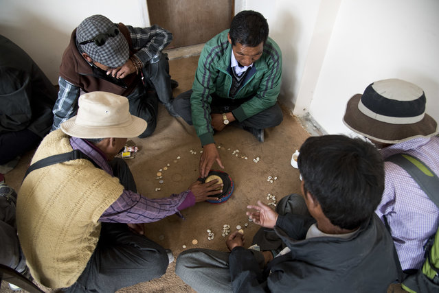 """In this August 20, 2016 photo, elders play """"chollo"""", a game where they shout as they throw the dice to bring good luck, in the city of Kaza, Spiti Valley, India. (Photo by Thomas Cytrynowicz/AP Photo)"""