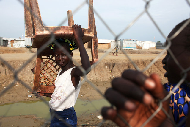 An internally displaced girl carries a chair inside a compound at the Protection of Civilians (POC) site in the UN base in Bentiu, South Sudan on July 16, 2018. (Photo by Andreea Campeanu/Reuters)