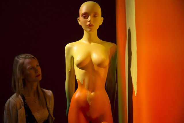 """A gallery assistant poses with the 2014 work """"To be or not to be"""" at a media viewing of the artist's exhibition """"Allen Jones RA"""" at the Royal Academy of Arts in London November 11, 2014. (Photo by Neil Hall/Reuters)"""