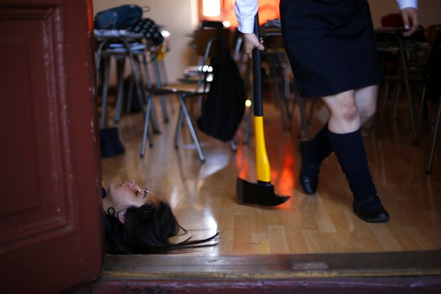 Students participate in an earthquake drill in their school in Santiago, November 13, 2014. Around one million people, which included students, teachers and parents, took part on Thursday in a drill that simulated a fictitious earthquake of a magnitude of 8.8 on the Richter scale, according to organizers. (Photo by Ivan Alvarado/Reuters)