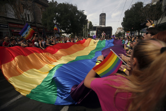 People wave flags during a gay pride march in Belgrade, Serbia, Sunday, September 18, 2016. Thousands of Serbian riot police have cordoned off central Belgrade for a gay pride march amid fears attacks from extremists in the predominantly conservative Balkan country seeking European Union membership. (Photo by Darko Vojinovic/AP Photo)
