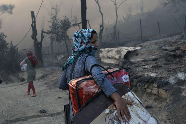 A migrant carries her belongings following a fire at the Moria camp for refugees and migrants on the island of Lesbos, Greece, September 9, 2020. Fire struck again Wednesday night in Greece's notoriously overcrowded refugee camp on the island of Lesbos, a day after a blaze swept through it and left thousands in need of emergency shelter. The fires caused no injuries, but they renewed criticism of Europe's migration policy. (Photo by Elias Marcou/Reuters)