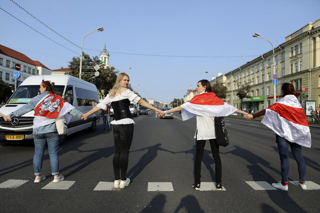 Women cover themselves with old Belarusian national flags as they block a road, during an opposition rally to protest the official presidential election results in Minsk, Belarus, Saturday, September 12, 2020. ( Photo by AP Photo/Stringer)