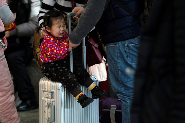 A child cries on a suitcase at Shanghai's Hongqiao Railway Station as the annual Spring Festival travel rush begins ahead of the Chinese Lunar New Year in Shanghai, China on February 1, 2018. (Photo by Aly Song/Reuters)