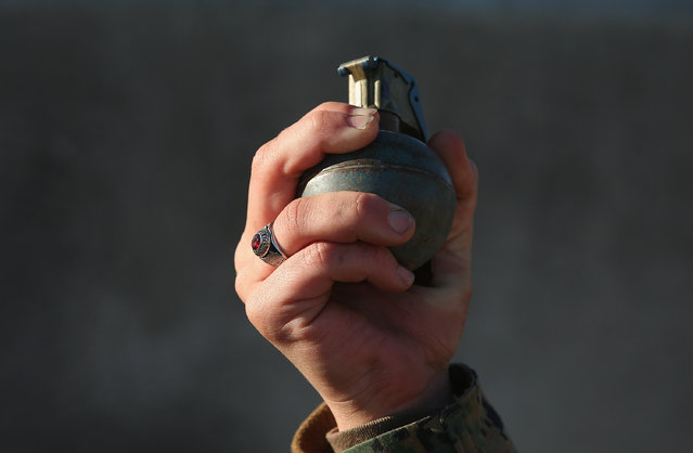 A female Marine prepares to throw a practice grenade during Marine Combat Training (MCT) on February 21, 2013 at Camp Lejeune, North Carolina.  Since 1988 all non-infantry enlisted male Marines have been required to complete 29 days of basic combat skills training at MCT after graduating from boot camp. MCT has been required for all enlisted female Marines since 1997. About six percent of enlisted Marines are female.  (Photo by Scott Olson)