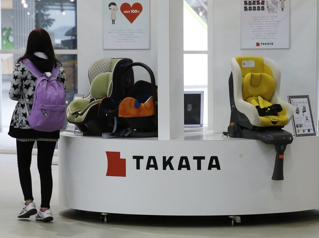 A visitor walks past displays of Takata Corp at a showroom for vehicles in Tokyo in this November 5, 2014 file photograph. Takata Corp said on November 19, 2014 it would work with U.S. safety regulators and automakers if an expanded recall of vehicles with potentially defective air bags is needed as urged by the National Highway Traffic Safety Agency (NHTSA). (Photo by Toru Hanai/Reuters)