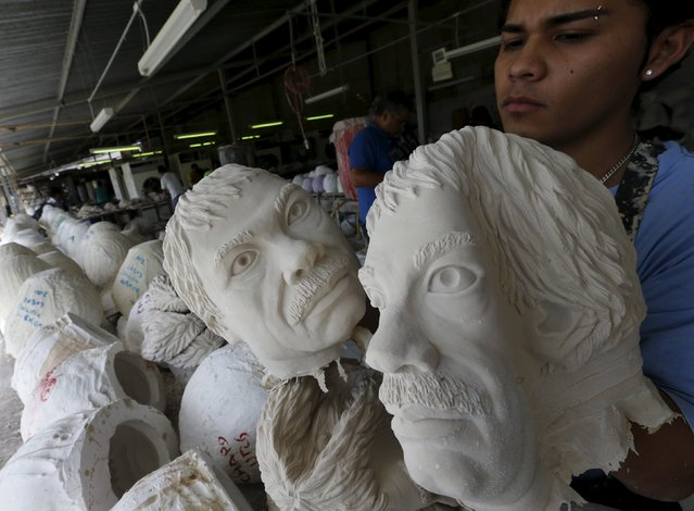 A employee holds Guzman masks as they are pulled from moulds at Grupo Rev in the Mexican city of Cuernavaca near Mexico City October 14, 2015. (Photo by Henry Romero/Reuters)