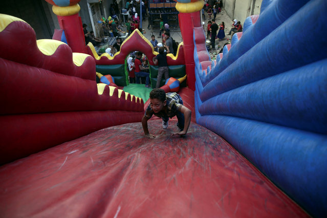 Children play inside an inflatable castle on the last day of Eid al-Adha celebrations in the rebel held besieged town of Hamouriyeh, eastern Ghouta, near Damascus, Syria September 15, 2016. (Photo by Bassam Khabieh/Reuters)