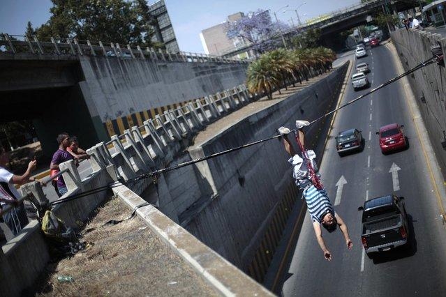 Luis Amezquita hangs upside down over the Periferico avenue during a slacklining practice in Guatemala City, February 24, 2013. According to Amezquita, this is the first time in Guatemala that anyone is attempting to practice slacklining over a street. Slacklining is an extreme sport that requires one to balance on a line anchored between two points. (Photo by Jorge Dan Lopez/Reuters)