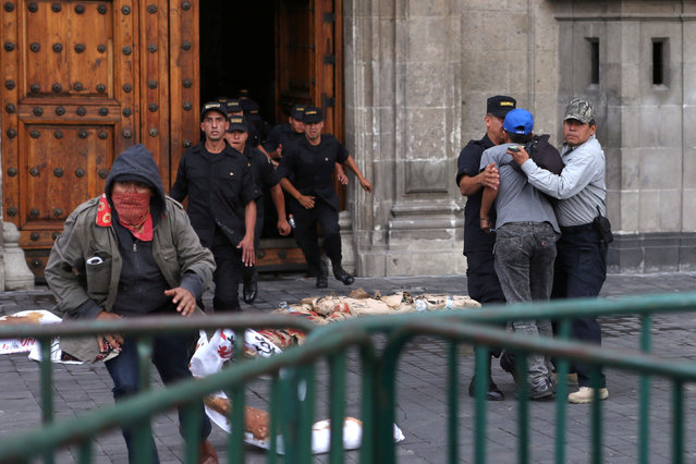 Police arrest a demonstrator while another escapes in a march to demand justice for the 43 missing students of Ayotzinapa College Raul Isidro Burgos to mark the two-year anniversary of their disappearance in the state of Guerrero, outside National Palace, in Mexico City, Mexico, September 26, 2016. (Photo by Edgard Garrido/Reuters)
