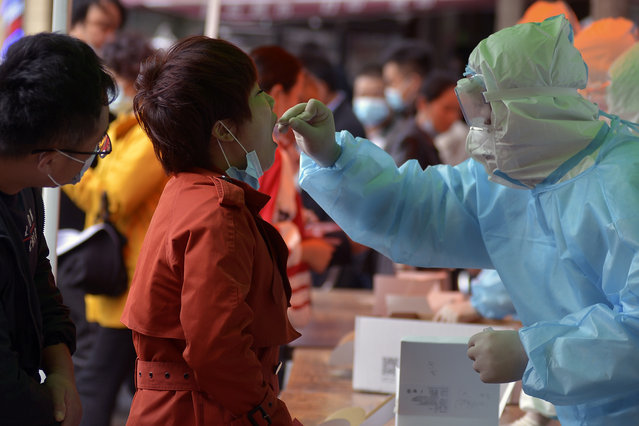 A medical staff takes a swab from a woman as residents line up for the COVID-19 test near the residential area in Qingdao in east China's Shandong province on Monday, October 12, 2020. Authorities in the eastern Chinese port city of Qingdao said Tuesday that they have completed coronavirus tests on more than 3 million people following the country's first reported local outbreak of the virus in nearly two months. (Photo by Chinatopix via AP Photo)