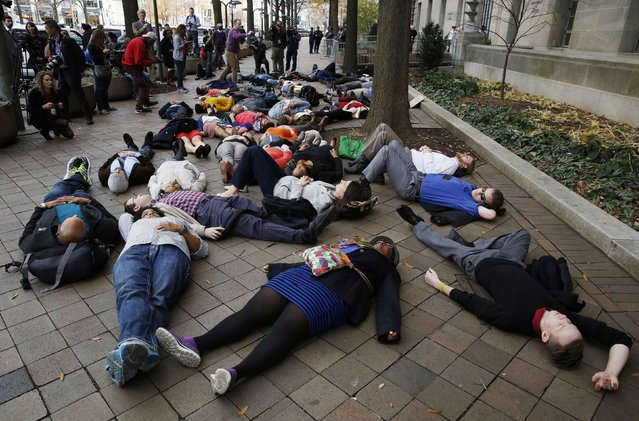 "Protestors stage a ""die-in"" as they rally against the Ferguson, Mo. Grand Jury exoneration of police officer Darren Wilson for his August 2014 shooting and killing of Michael Brown while, at the U.S. Justice Department in Washington, December 1, 2014. U.S. President Barack Obama asked Congress on Monday for $263 million for the federal response to the civil rights upheaval in Ferguson, Missouri, and is setting up a task force to study how to improve modern-day policing. (Photo by Larry Downing/Reuters)"