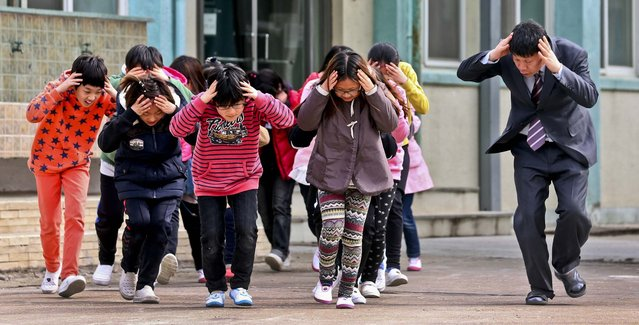 Elementary students and a teacher rush to a shelter during a civil defense drill against possible North Korea attack on Baeknyeong Island, on March 19, 2013. The United States is flying nuclear-capable B-52 bombers on training missions over South Korea to highlight Washington's commitment to defend an ally amid rising tensions with North Korea. (Photo by Yonhap, Bae Jung-hyun/Associated Press)