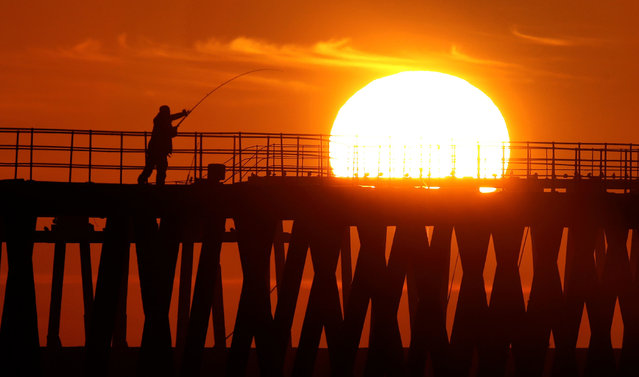 A man fishing in the early morning light as the sun rises over Blyth pier in Northumberland on the first day of Meteorological autumn, on September 22, 2020. (Photo by Owen Humphreys/PA Images via Getty Images)