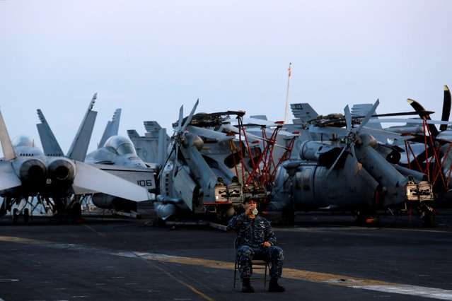 A sailor drinks, as he guards among aircraft, aboard the U.S. Navy aircraft carrier, USS Carl Vinson, after it docked at a port in Danang, Vietnam March 5, 2018. For the first time since the Vietnam War, a U.S. Navy aircraft carrier is paying a visit to a Vietnamese port, seeking to bolster both countries' efforts to stem expansionism by China in the South China Sea. (Photo by Reuters/Kham)