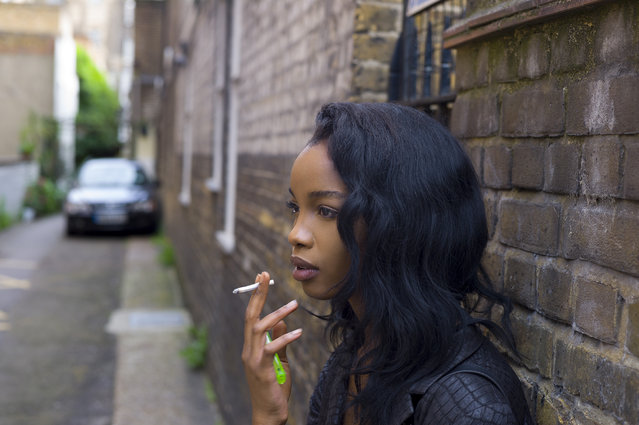 Woman leaning on the wall smoking a cigarette. Portrait of young stylish Londoner in urban environment. (Photo by Justin Case/Getty Images)