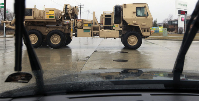 A view motorists have grown accustomed seeing, a military truck made by Oshkosh Corp. is taken for a test drive Thursday, April 11, 2013 in Oshkosh, Wis. Faced with deep cuts in U.S. military spending, and the end of the wars in Iraq and Afghanistan, Oshkosh Corp. is laying off 900 employees in its defense division based in Oshkosh. Approximately 700 hourly workers at the state's largest manufacturer will lose their jobs in mid-June, followed by approximately 200 salaried employees through July. (Photo by Mark Hoffman via The Journal Sentinel)