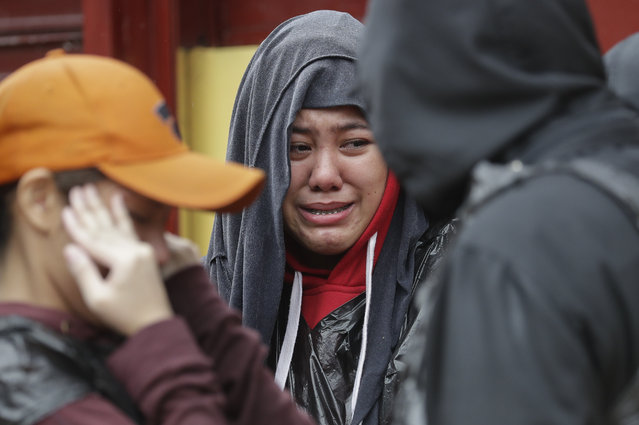 Residents cry as they ask rescuers to bring out their trapped relatives while floods continue to rise in Marikina, Philippines due to Typhoon Vamco on Thursday, November 12, 2020. (Photo by Aaron Favila/AP Photo)