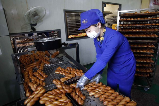 In this October 28, 2020, file photo, an employee oversees the making of bread items at the Songdowon General Foodstuff Factory in Wonsan, Kangwon Province, North Korea. (Photo by Jon Chol Jin/AP Photo)