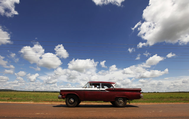 A car drives on a road near the village of Quivican, near Havana, October 11, 2009. (Photo by Desmond Boylan/Reuters)