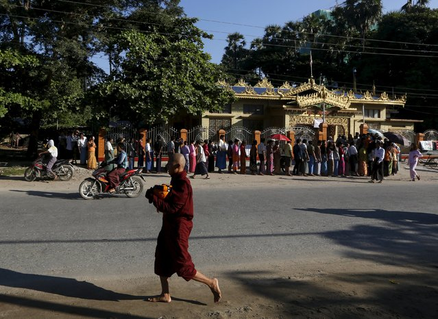 A monk walks past a Buddhist prayer hall where people queue to vote during the general election in Mandalay, Myanmar, November 8, 2015. (Photo by Olivia Harris/Reuters)