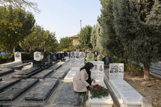 Ayat Hosseini, an Iranian woman who lost her husband, Soheil due to coronavirus, puts flowers on his grave at a cemetery in south of Tehran, Iran on November 18, 2020. (Photo by Majid Asgaripour/WANA (West Asia News Agency) via Reuters)