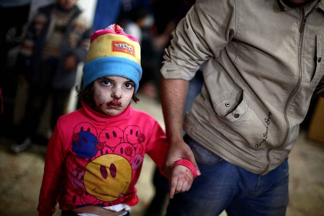 A wounded child walks at a makeshift hospital in the besieged rebel-held town of Douma after being injured in a reported airstrike by government forces on December 23, 2014. Douma, a rebel bastion northeast of the capital, has been under government siege for more than a year, with residents facing dwindling food and medical supplies. (Photo by Abd Doumany/AFP Photo)