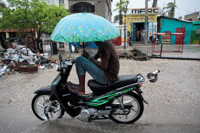 A man protects himself from rain as he drives a motorbike after Hurricane Matthew in Les Cayes, Haiti, October 17, 2016. (Photo by Andres Martinez Casares/Reuters)