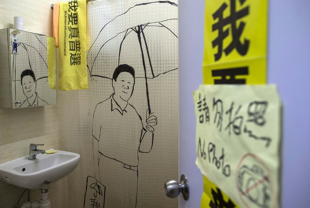 "A painting of Chinese President Xi Jinping holding an umbrella is seen on the toilet wall in a guesthouse in Hong Kong December 30, 2014. Set up in a small apartment in the Causeway Bay shopping district, the guesthouse that gives what it calls ""Umbrella Revolution Occupation Experience"" charges guest HK$100 (US$13) a night to stay in a tent surrounded by pro-democracy banners. (Photo by Tyrone Siu/Reuters)"